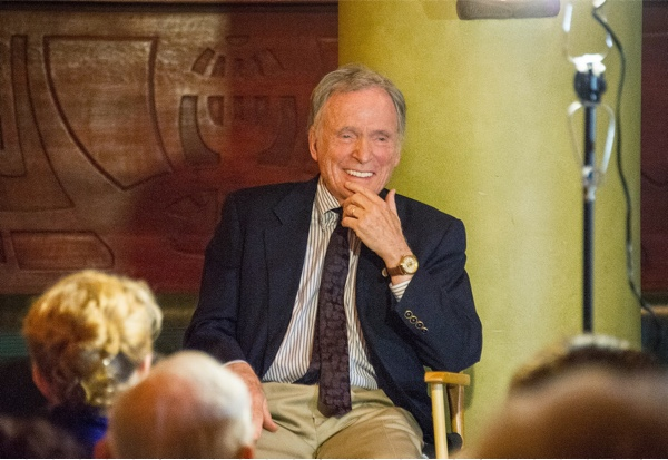 Dick Cavett smiling and sitting before an audience.