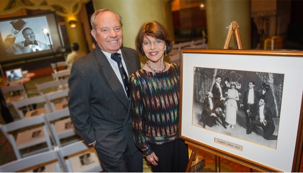 Ron and Harriet standing next to a framed black and white photo.