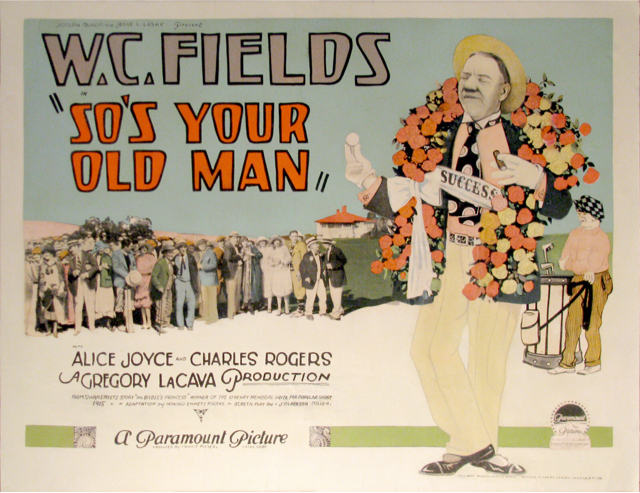 W.C. Fields wearing a garland of roses around his neck while holding-up a golf ball.