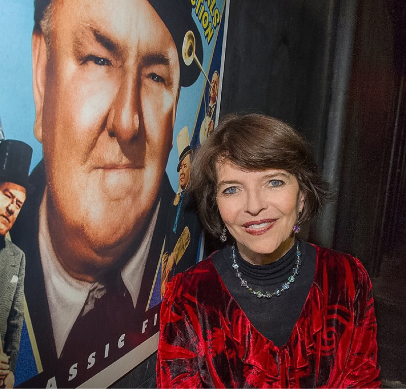 Dr. Harriet Fields standing next to W.C. Fields: Comedy Essentials Collection poster.